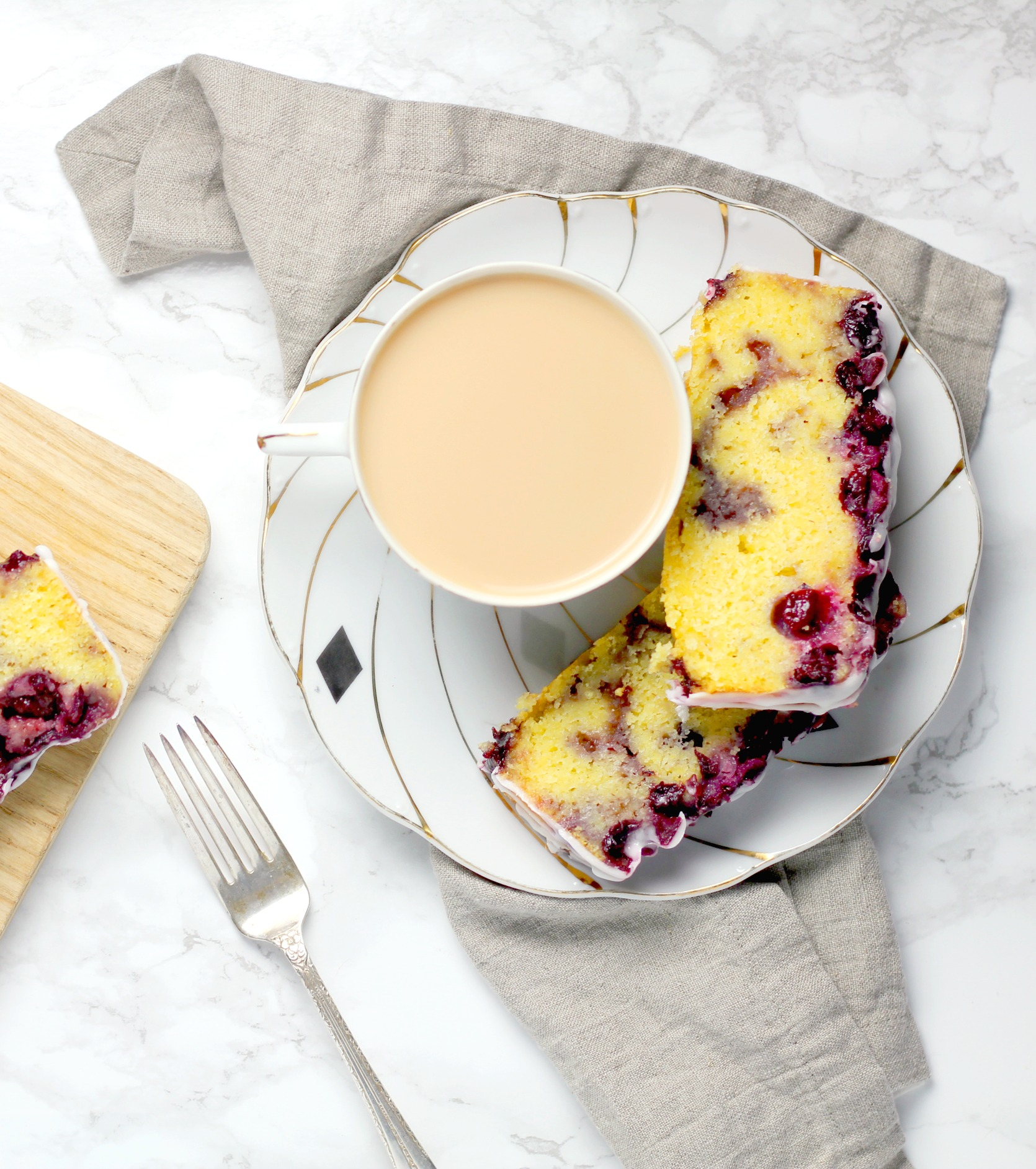 two slices of blueberry upside down lemon bread on a saucer with a cup of coffee