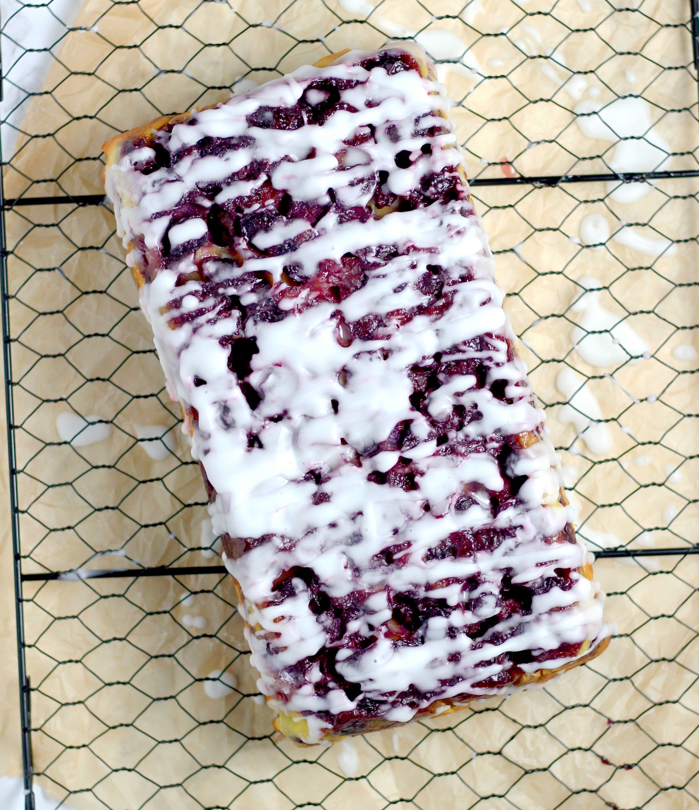 cooling rack with a loaf of blueberry upside down bread with a powdered sugar glaze