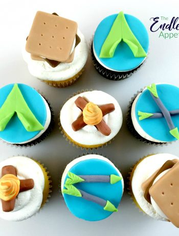 8 cupcakes with fondant toppers that look like s'mores, a bonfire and arrows