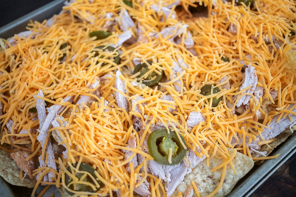 Tortilla chips with pulled pork, jalapenos and cheese on cookie sheet