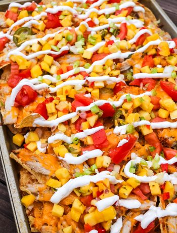 Hawaiian pulled pork nachos with pineapple and mango pieces on a baking sheet
