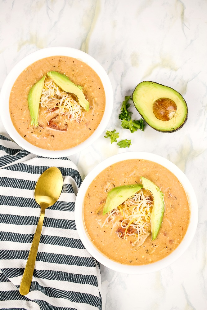 two bowls of Mexican chicken soup with an avocado and gold spoon in the background