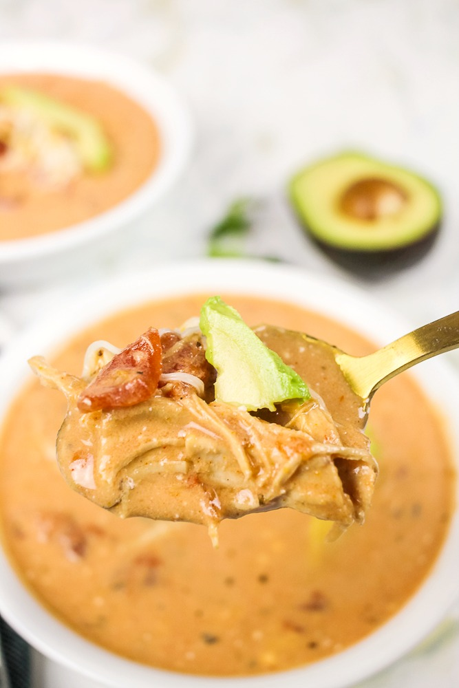 spoon holding a bite of chicken taco soup with an avocado and tomato