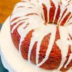 red velvet bundt cake with powdered sugar glaze on white cake stand