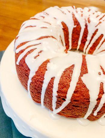 red velvet bundt cake with powdered sugar glaze on white cake stand