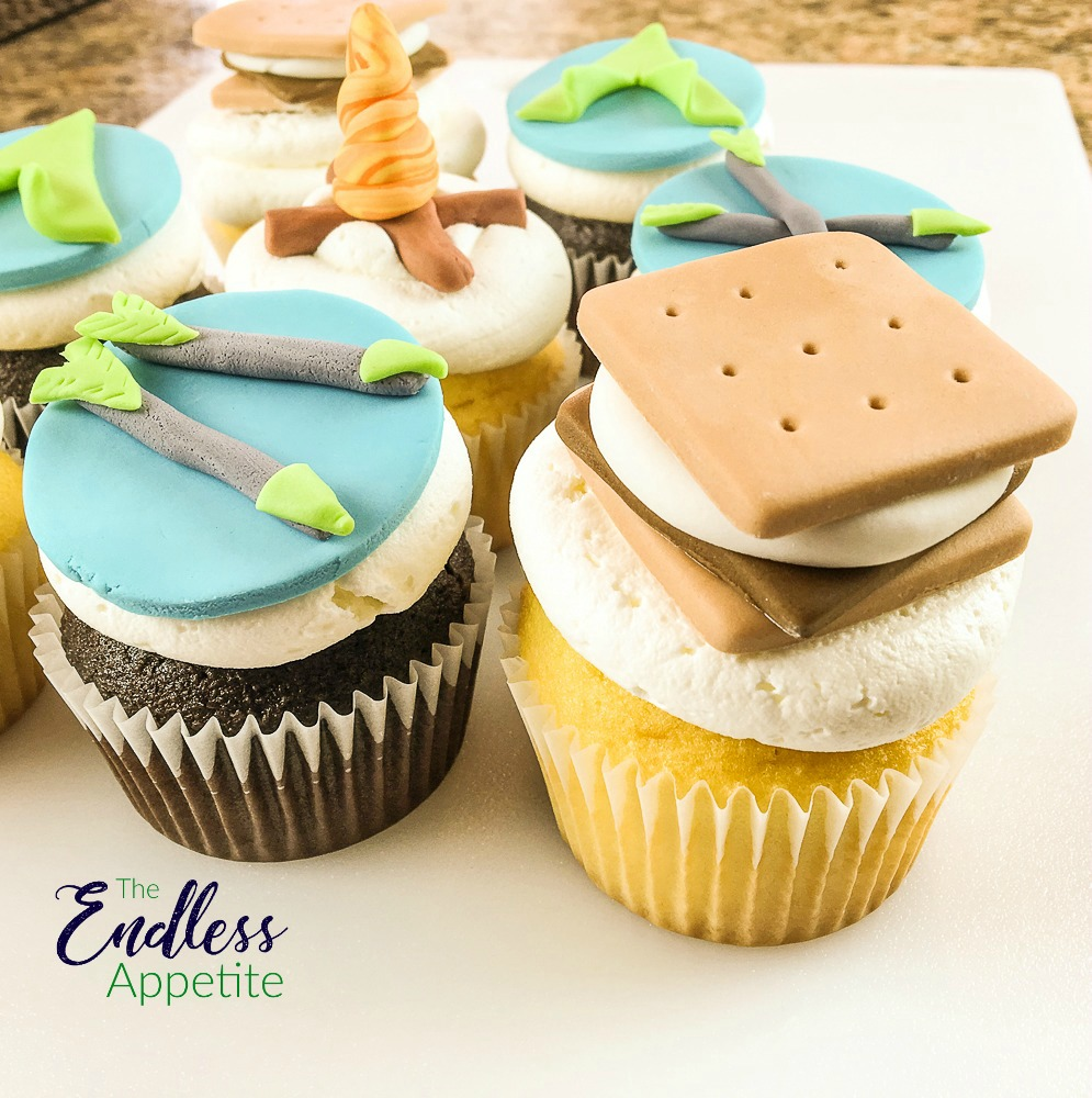 cupcakes with fondant toppers that look like s'mores and arrows