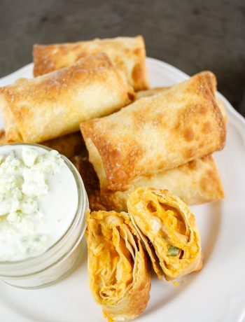 a white plate with buffalo chicken egg rolls and a mason jar of blue cheese dip