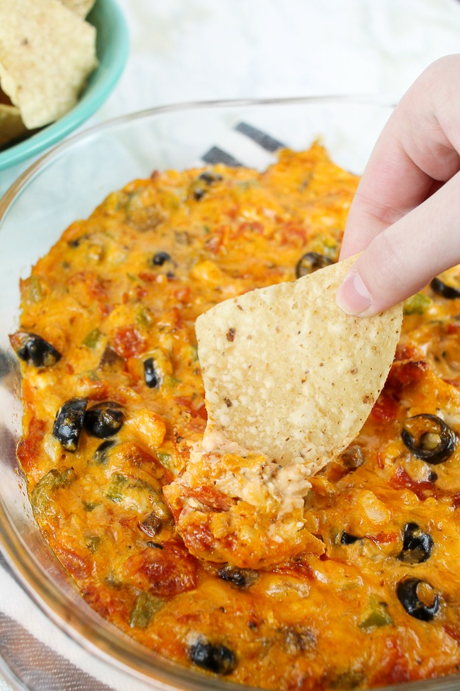 a tortilla chip dipping into a hot pizza dip