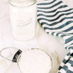 measuring cup and mason jar filled with homemade bisquick and a striped tea towel