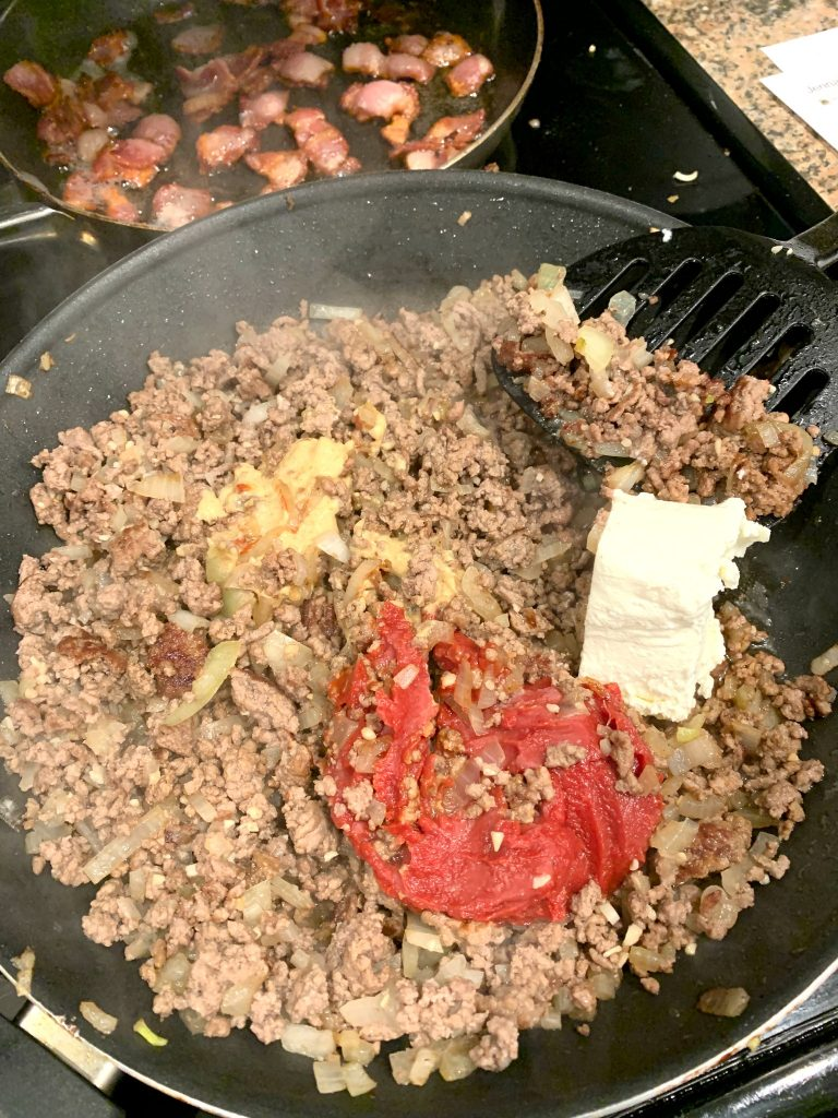 skillet with ground beef, ketchup, mustard and cream cheese for low carb bacon cheeseburger casserole