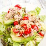 plate with greens, avocado halves and Mediterranean Tuna Salad