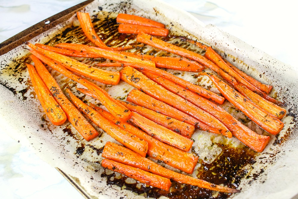 Roasted carrots with a honey brown sugar glaze on a cookie sheet