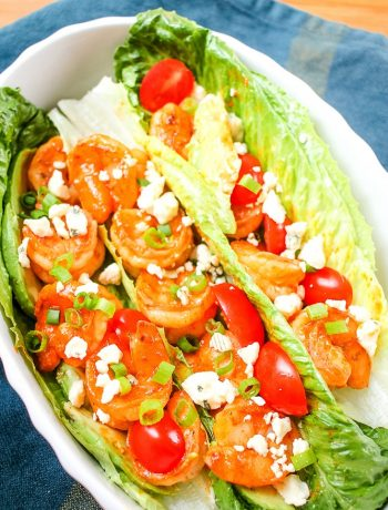 white platter with buffalo shrimp lettuce wraps and toppings