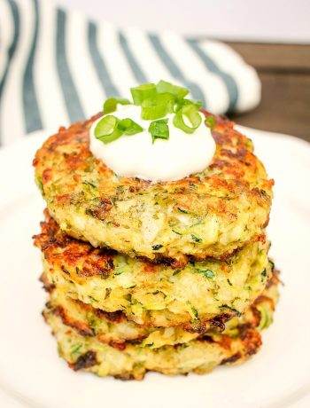 4 zucchini fritters stacked on a white plate with sour cream and green onions on top