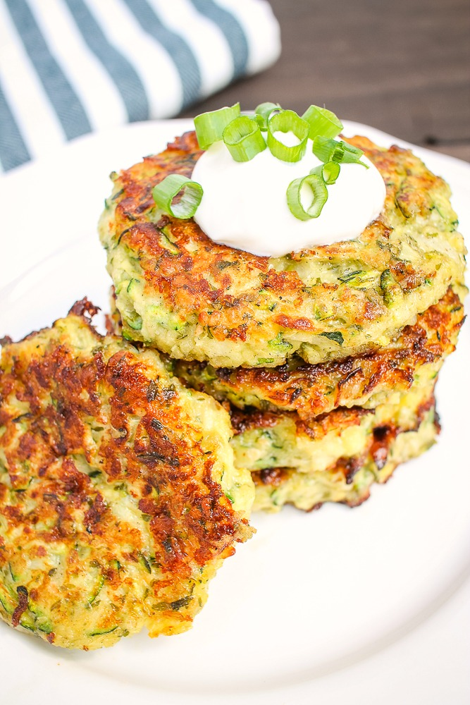stack of zucchini parmesan cakes with one laying against them