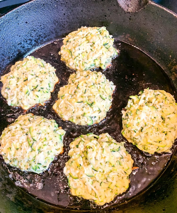parmesan zucchini fritters in a cast iron skillet