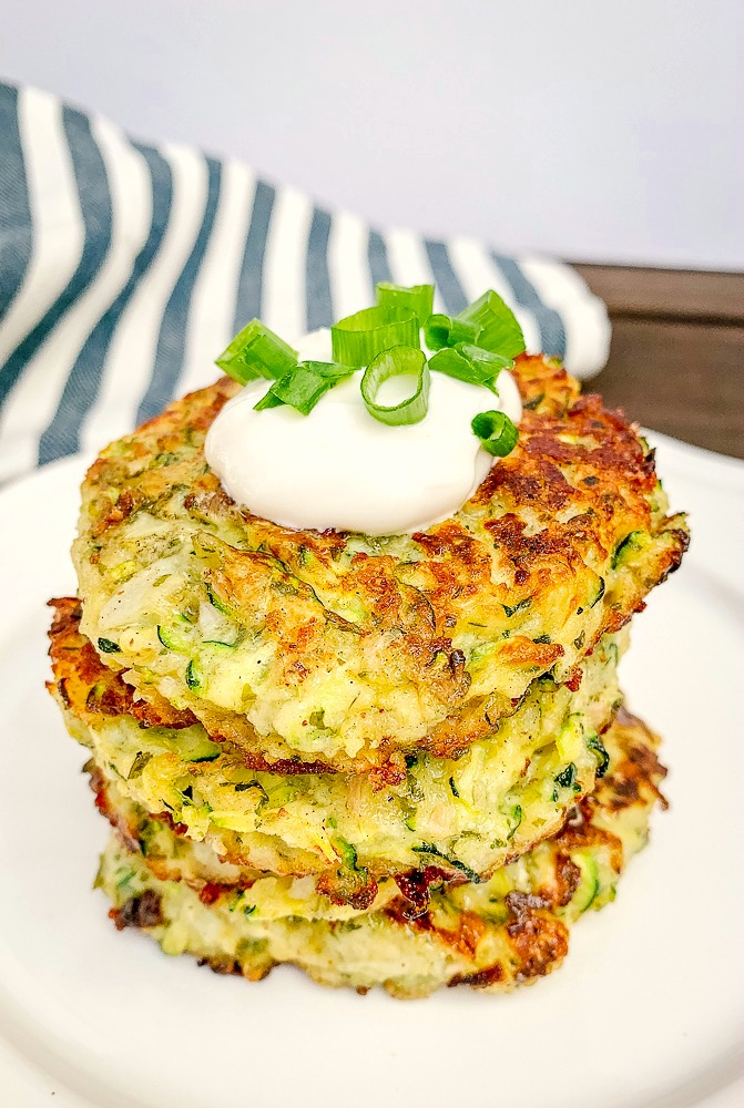 4 zucchini parmesan cakes on a plate with sour cream and green onions