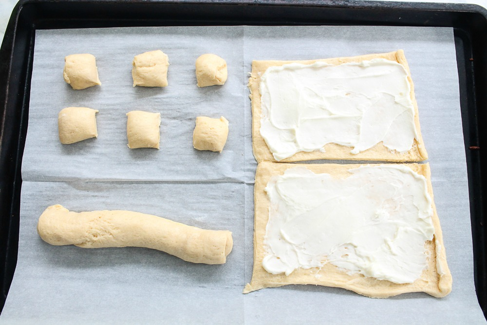 cookie sheet lined with parchment paper that shows the steps to make cream cheese filled crescent roll danishes