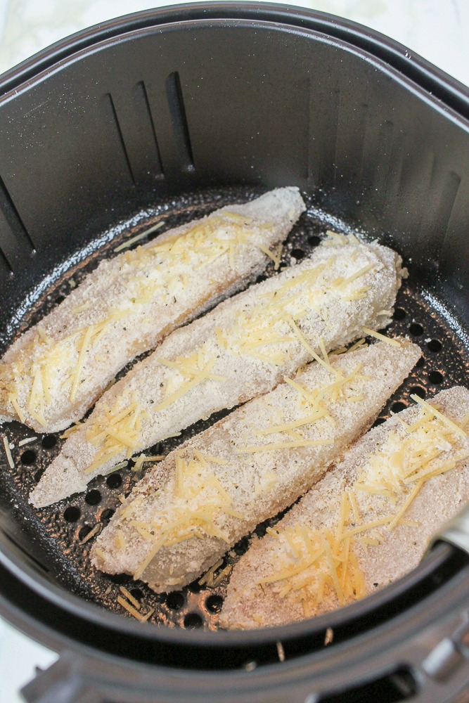 4 parmesan crusted fish fillets in an air fryer insert
