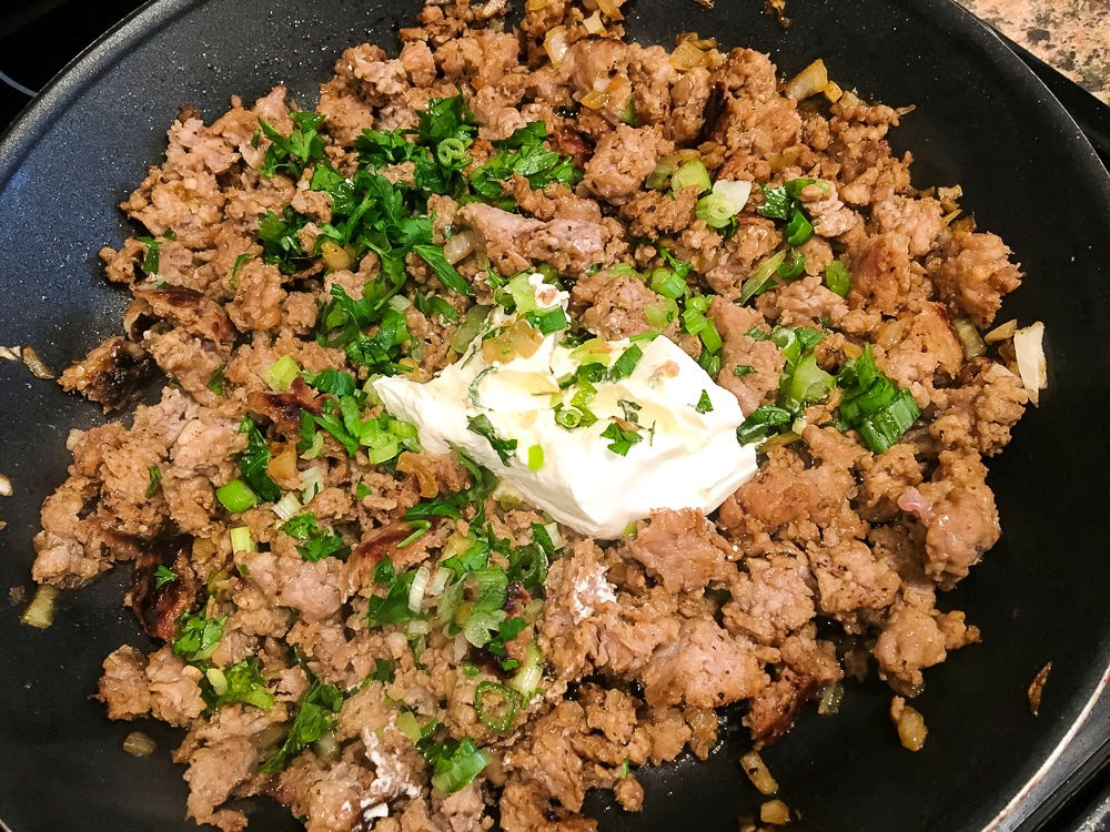 skillet with cooked sausage, cream cheese and fresh parsley
