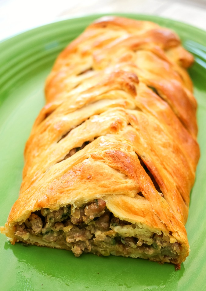 green platter with sausage crescent roll braid cut open to show the inside