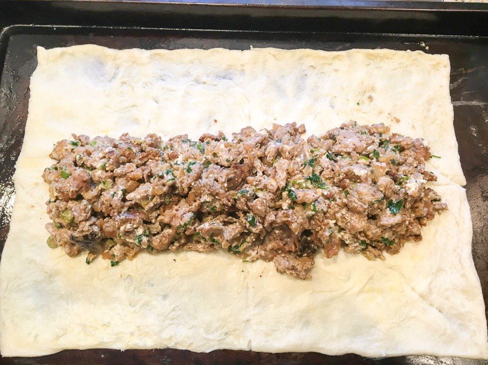 a rectangle of crescent roll dough with the sausage cream cheese mixture down the center