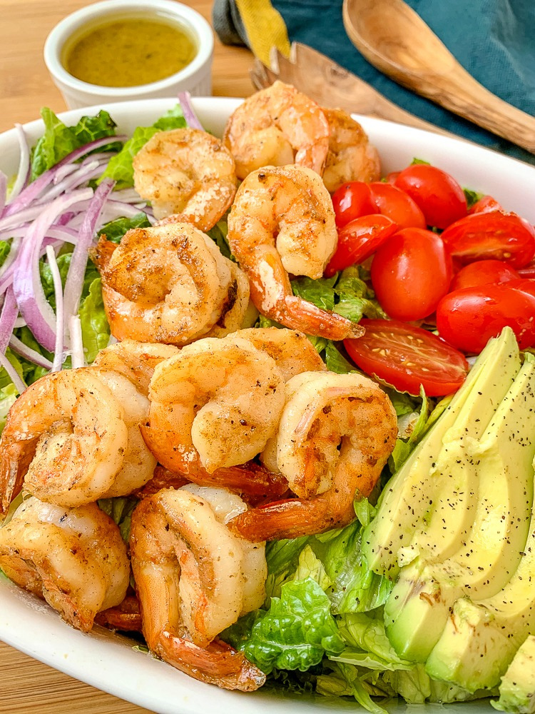 shrimp salad with avocados, tomatoes, red onion and honey lime dressing in a small cup in the background
