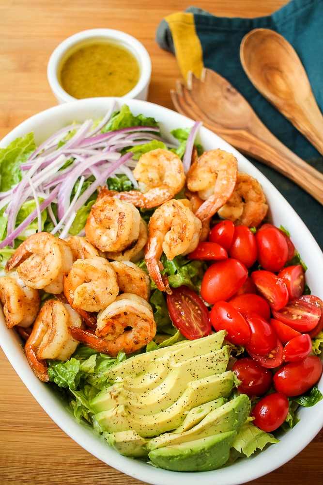 a white oval dish with shrimp avocado salad and a honey lime dressing in a smaller white dish