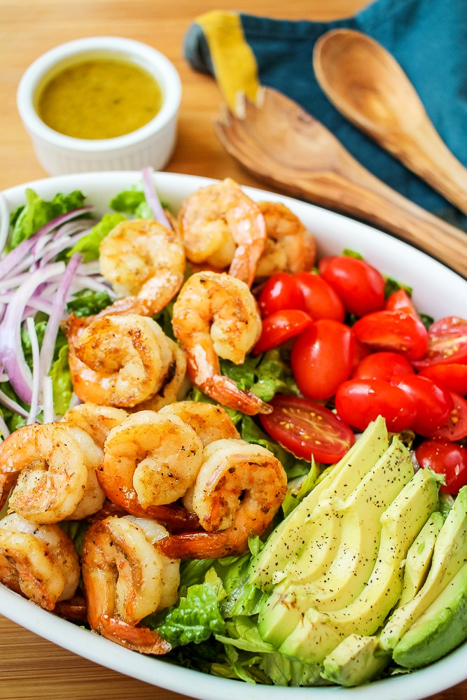 shrimp avocado salad with honey lime dressing, avocados, red onions and tomatoes
