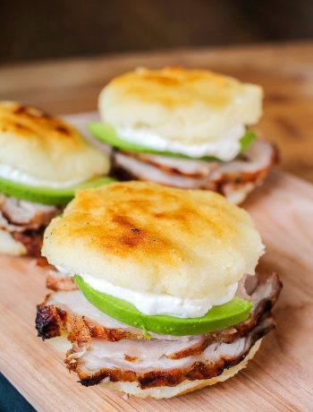 Venezuelan arepa sandwich filled with grilled pork, avocados and sour cream