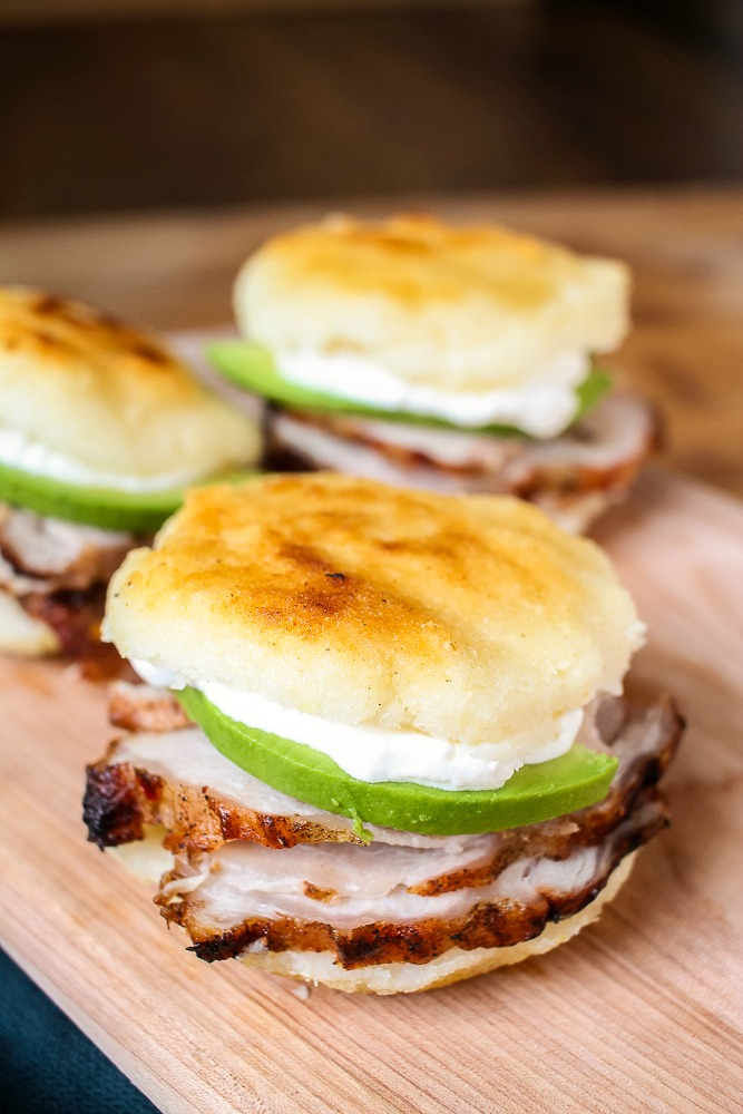 Venezuelan arepa stuffed with sliced pork, avocado and sour cream
