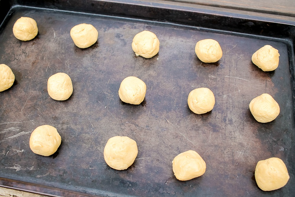 peanut butter cookie dough lined up on a cookie sheet