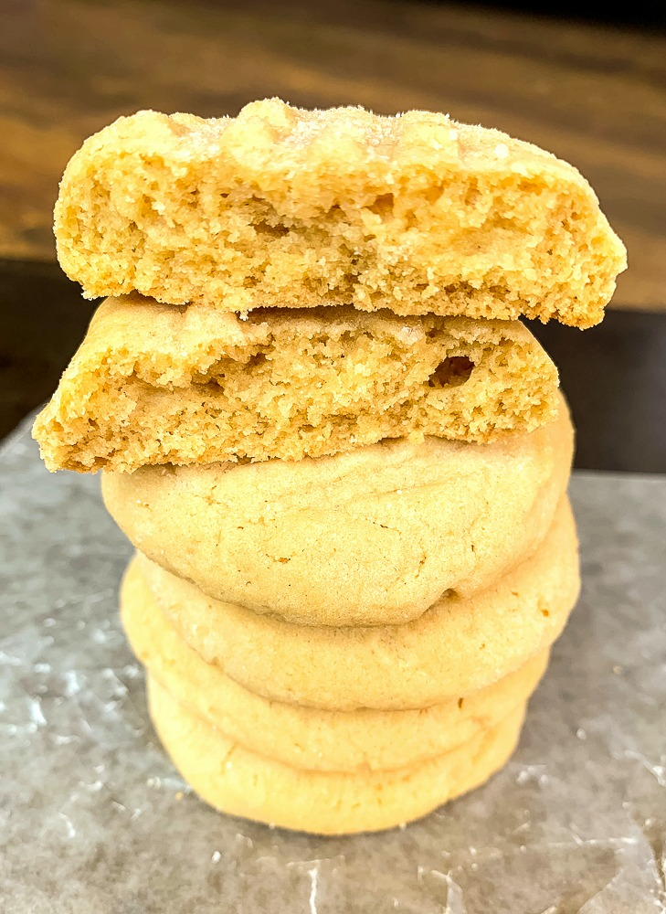a pile of peanut butter cookies with one split open to see how chewy it is