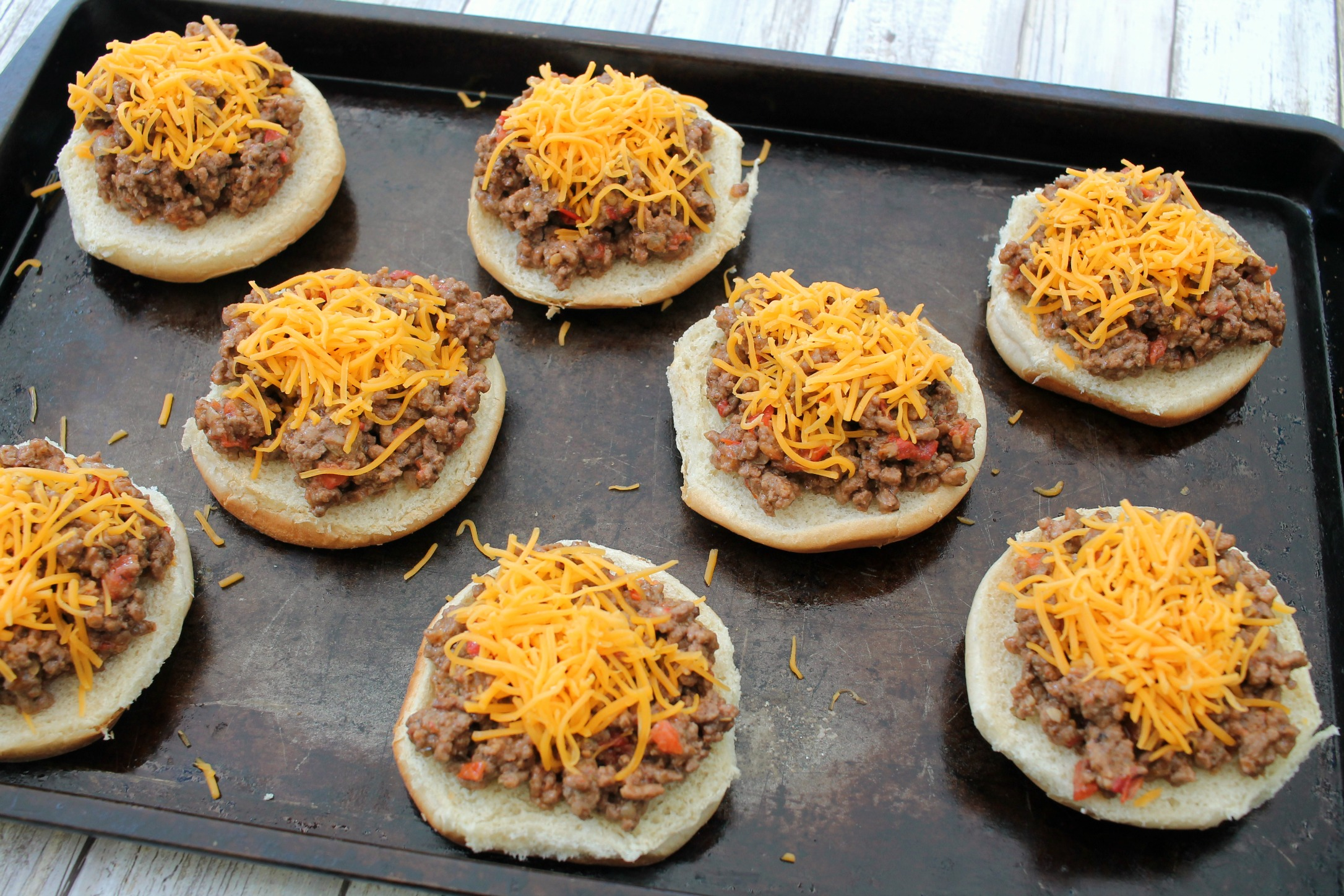cookie sheet lined with hamburger buns with cheeseburger sloppy joes with shredded cheese on top