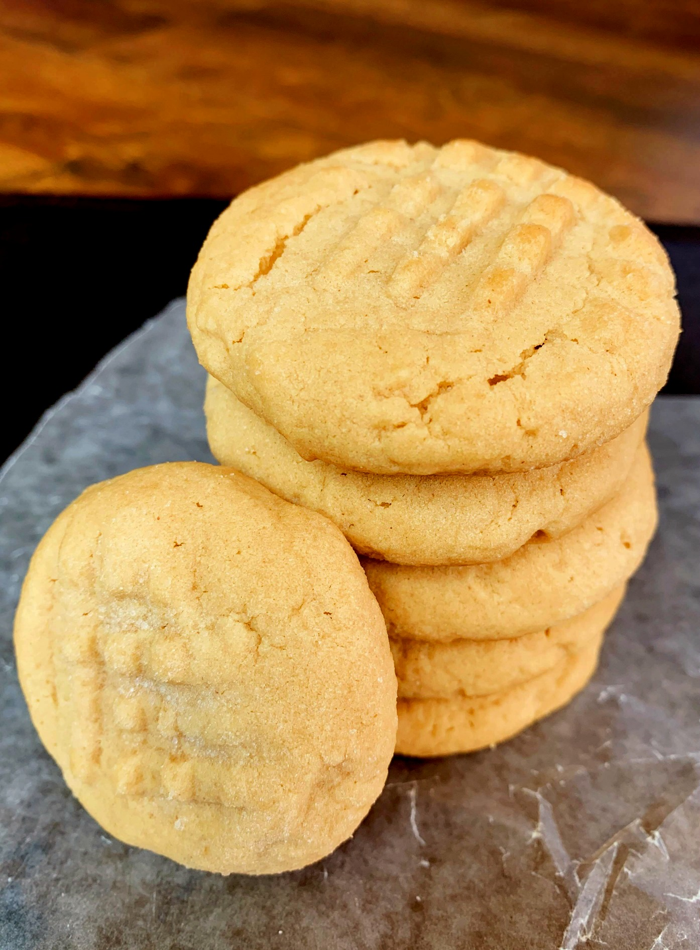 a pile of 4 old fashioned peanut butter cookies with one leaning against it