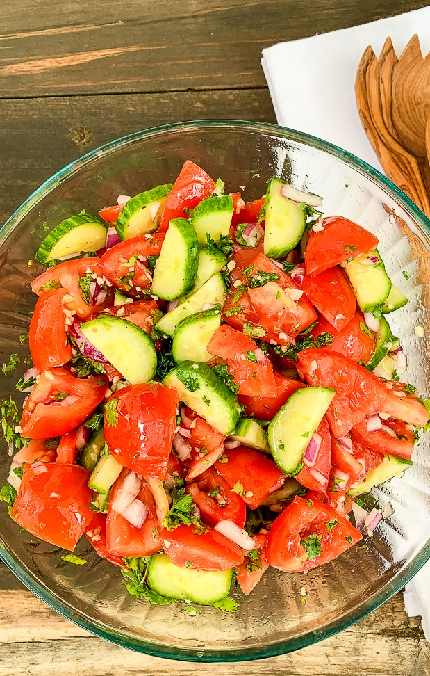 glass bowl of tomato and cucumber salad recipe with a white towel in the background