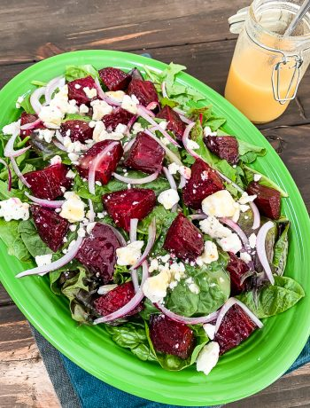 a green platter with roast beetroot salad with a small jar of honey dijon salad dressing beside it