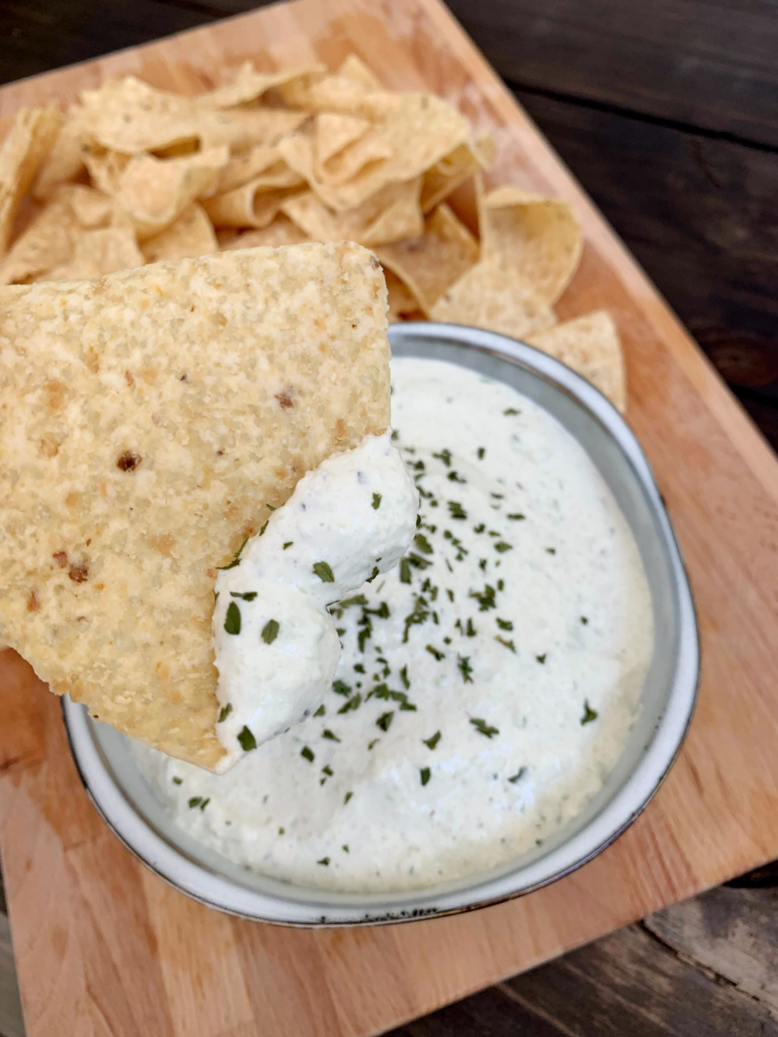 bowl of cucumber cream cheese dip with a tortilla chip dipped in the dip