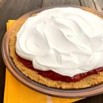 a glass pie dish with a graham cracker crust, no bake strawberry pie filling and cool whip on top