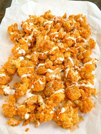 parchment paper with single layer of buffalo cauliflower bites with a blue cheese drizzle over them