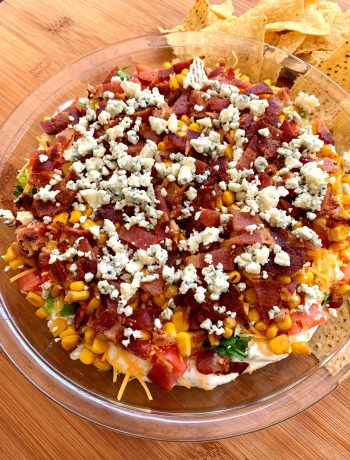 glass pie plate with loaded bacon and corn dip