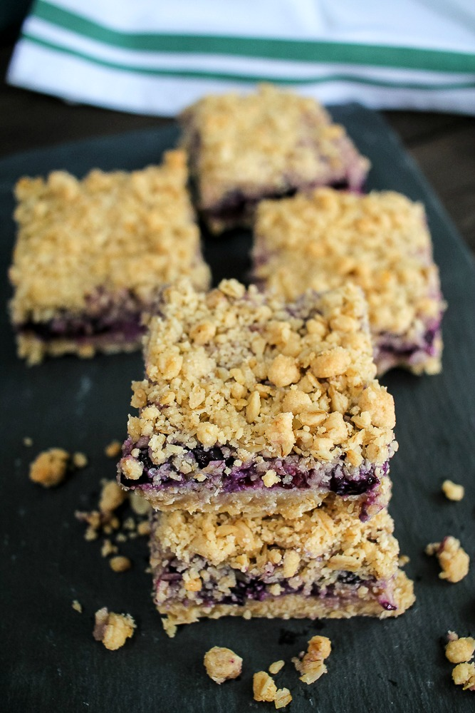 blueberry crumble bars on a piece of slate with a dish towel in the background