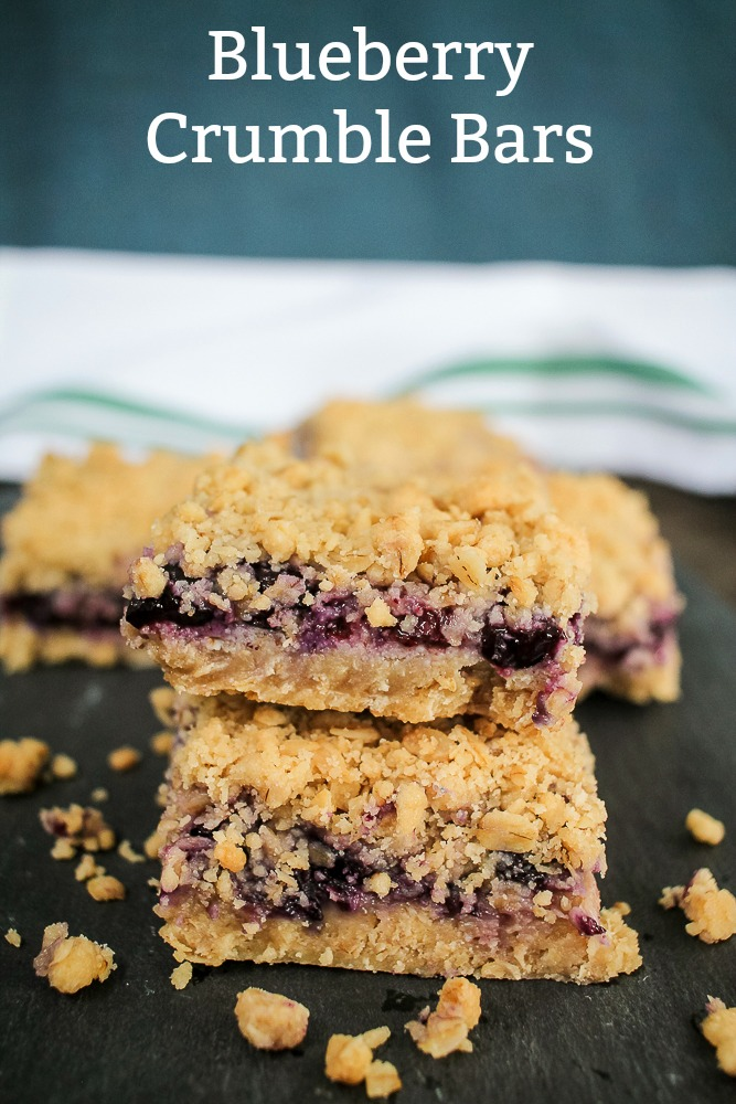 blueberry crumble bars stacked on top of each other with more bars in the background