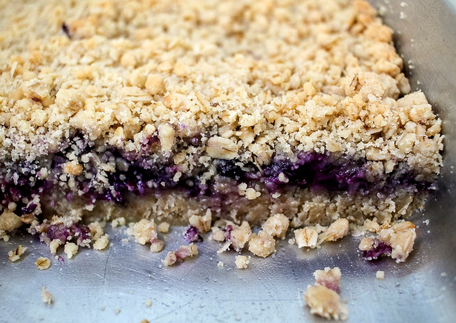 a metal pan with blueberry crumb bars with pieces cut away