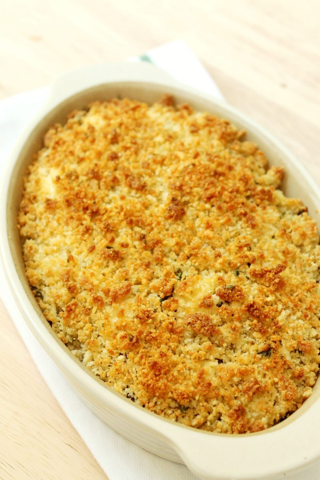 an oval stoneware dish with a golden brown crumb topping