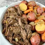 white round dish with shredded chuck roast and red potatoes and carrots
