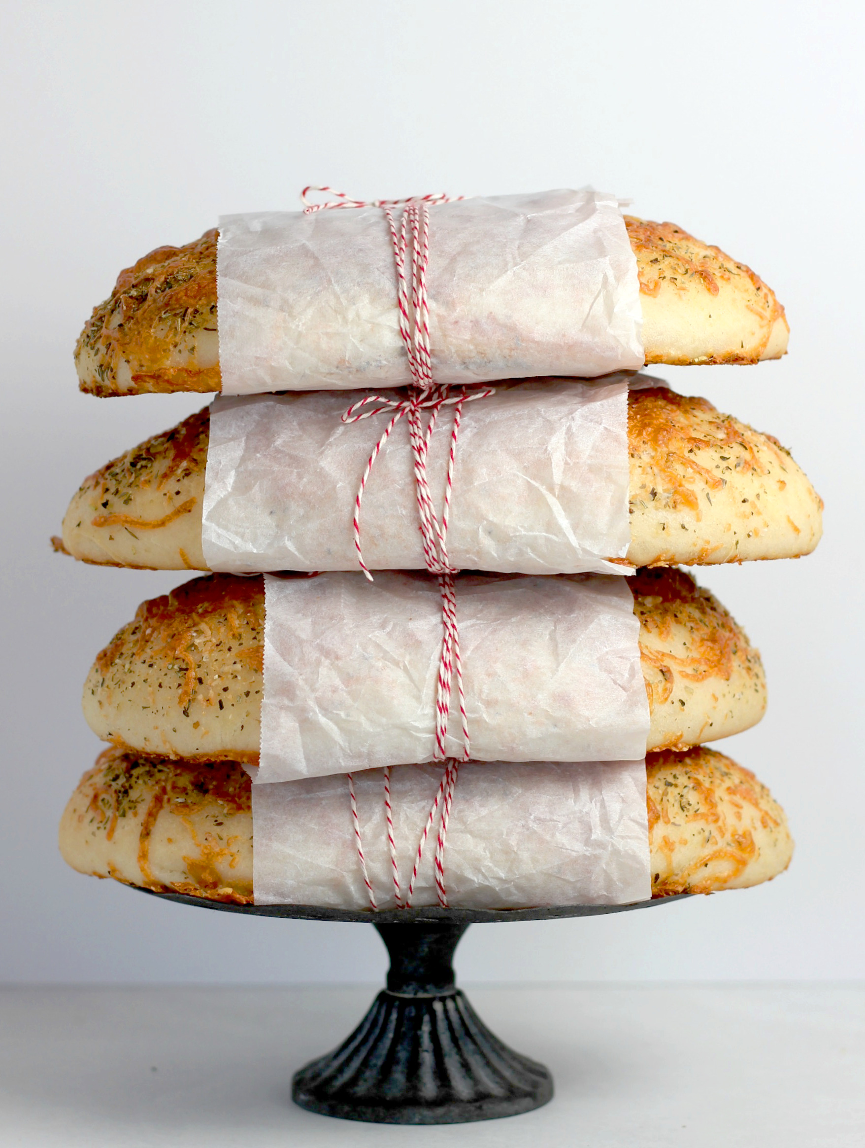 4 loaves of Italian cheese bread stacked on top of each other and wrapped with parchment paper and twine