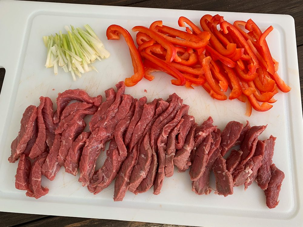 white cutting board with beef, red pepper and green onions all cut into strips
