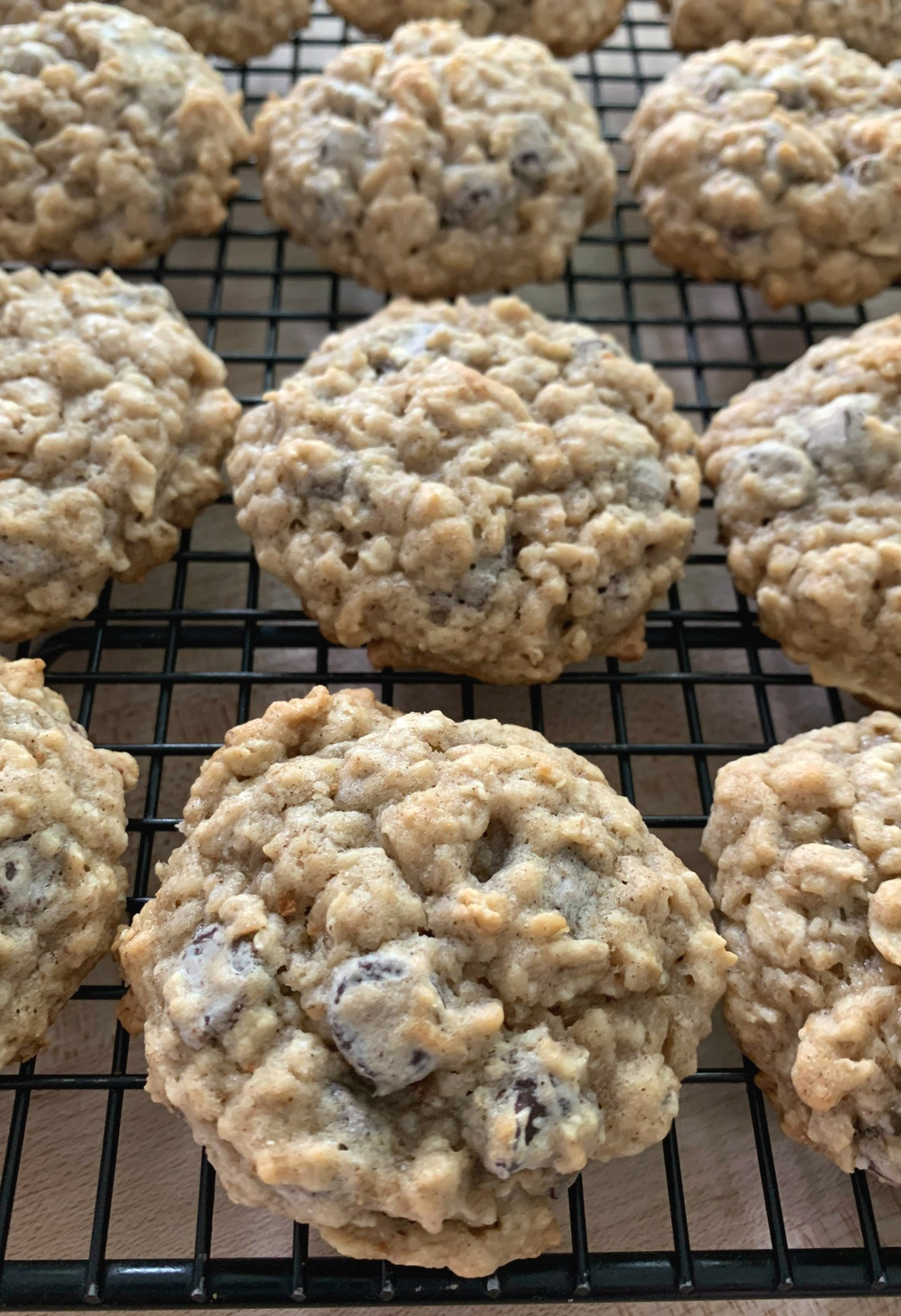 a black cooling rack with rows of banana oatmeal chocolate chip cookies