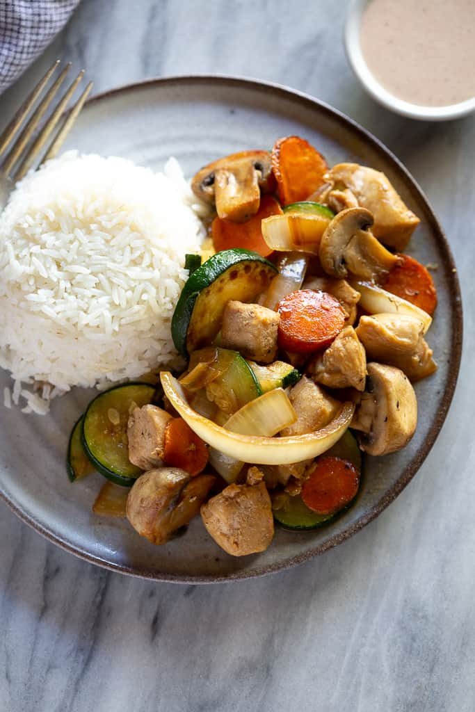 plate of hibachi chicken and veggies with rice on the side